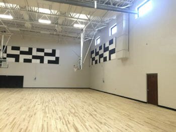 Sound Silencer material by Acoustical Surfaces being installed in a gym.