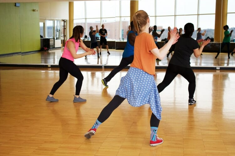 A group of people dancing in a gym with a mirror and Acoustical Surfaces materials.