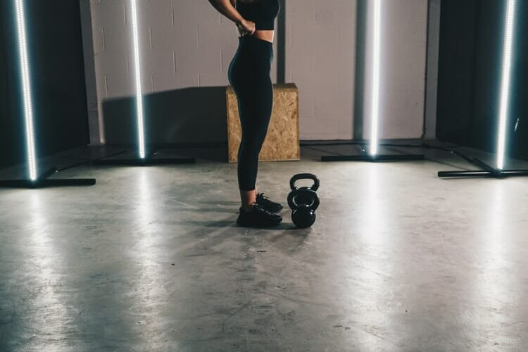 A woman working out in a gym with Acoustical Surfaces materials.
